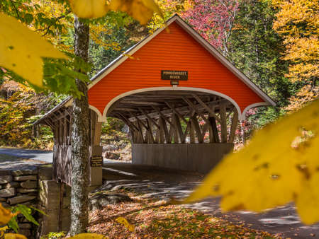 Red covered bridge in Fanconia New Hampshire during Fall season 스톡 콘텐츠