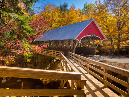 Red covered bridge during the fall season in Franconia, NH Foto de archivo