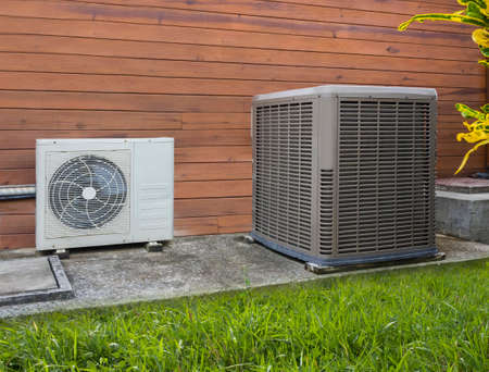 conditioner: Two different sized air conditioning heat pumps on the side of a house