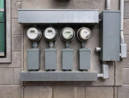 Line-up van vier elektrische energie meter aan de zijkant van appartementencomplex