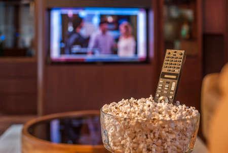 Klaar om TV te kijken met kom popcorn en afstandsbediening