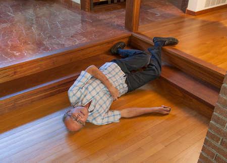 para baixo: Homem sênior no chão depois de cair para baixo os passos e pedindo ajuda com bip