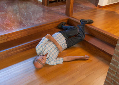 Senior man on the floor after falling down the steps and calling for help with beeper Stockfoto
