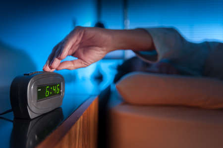 annoyed: Woman pressing snooze button on early morning digital alarm clock