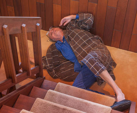 Senior man just fell down the stairs Stock Photo