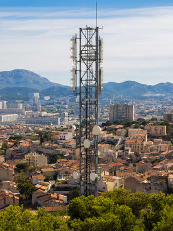 Cell phone tower over a town in southern France Stock Photo