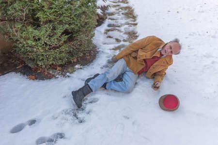 Senior man slipping on ice on his walkway