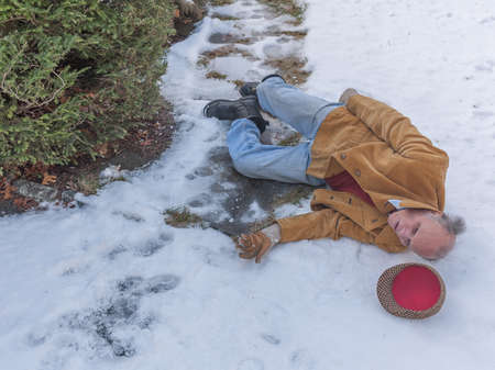 accidental: Senior man slipping on ice on his walkway Stock Photo