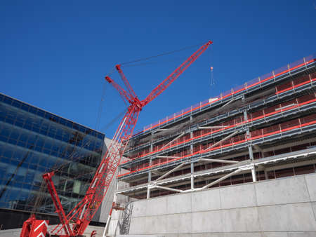 New comercial building construction with big crane lifting side panels Imagens