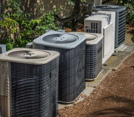 Heating and air conditioning units in back of an apartment complex Stock Photo