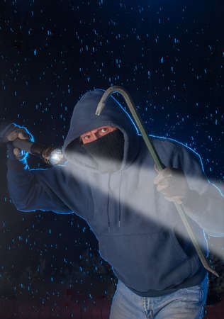 Burglar prowling on a rainy night looking to break into a house
