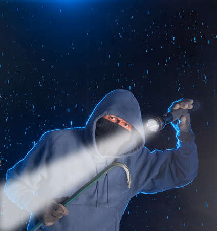 Intruder prowling on a rainy night looking to break into a house. Stock Photo