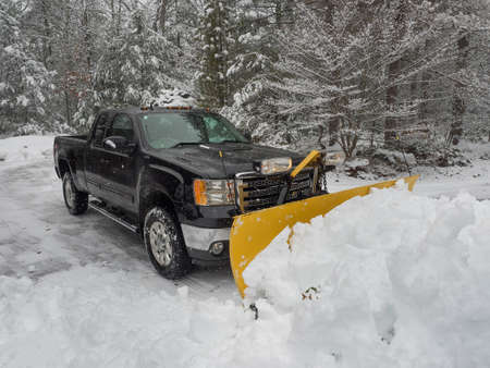 Truck snow plow clearing a parking lot after storm