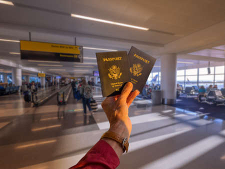 Hand holding two American passports in front of a boarding airline gate