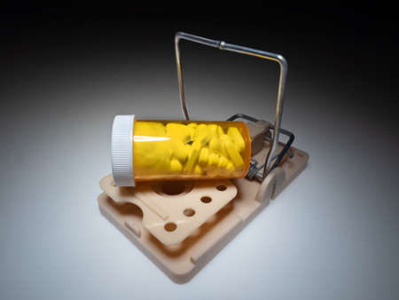 Mousetrap with medical bottle full pills. Drug cost and addiction concept