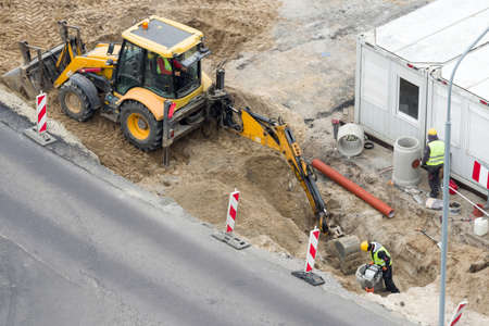 construction works in the street renovation carried out with the help of machines and people