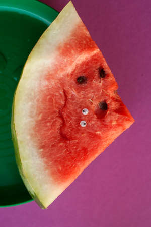 A piece of sliced ​​watermelon with eyes lying on a plate. On a purple background
