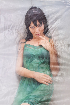 cellophane: Photo in studio of Dolly Body Woman covered with Cellophane and alluring eyes Stock Photo