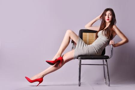 椅子に座ってポーズ縞模様のドレスの女の子 写真素材