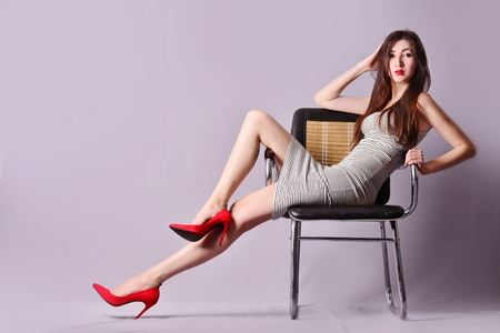 girl in a striped dress posing sitting on a chair