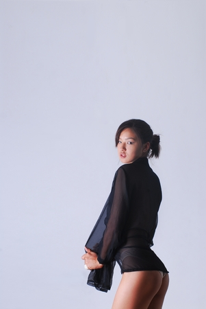 Young Asian woman in a black transparent blouse and beautiful figure on a white background