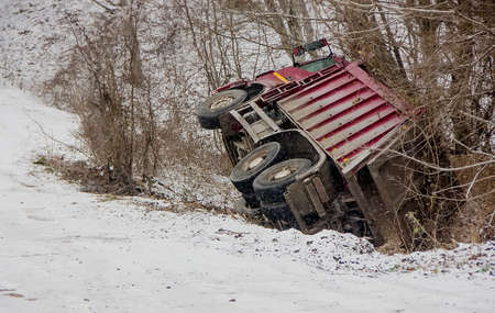 loaded truck overturned on a slippery winter road. clear day