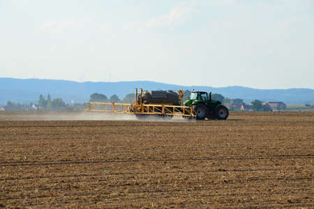 treating: Plowed field with a tractor treating the soil Stock Photo