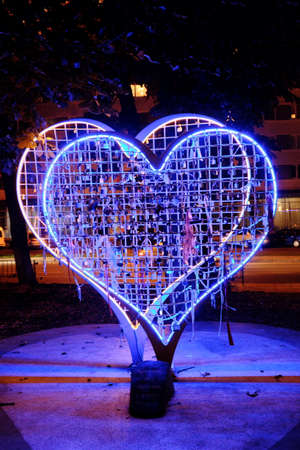dearness: Illuminated blue sculpture of two hearts in night city Lviv