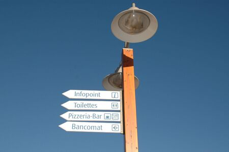 toilette: a street lamp with signs of information, bar, cash point, toilette Stock Photo