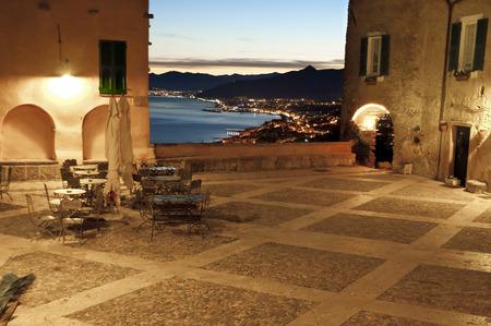 このファイルは、特定の Borgio verezzi で夜に、イタリアン ・ リヴィエラのパノラマ ビューを表します。カフェ, ものいくつかのテーブルがあります