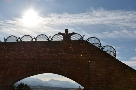 Silhouette of young man relaxing on a little bridge