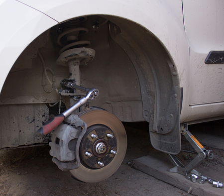 pawl: Car wheel is being maintained on  car repair station.