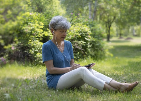 uses a computer: Smiling senior gray-haired woman sitting on green grass and listening to music with tablet computer. Eldery woman uses tablet.