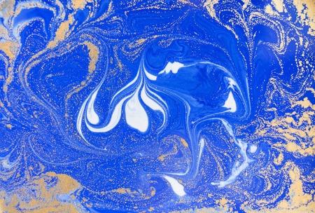 Blå och gyllene flytande konsistens. Akvarell handritad marmorering illustration. Bläck marmorbakgrund. Stockfoto