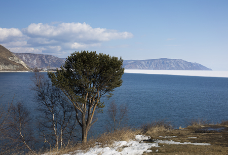 Baikal lake spring landscape view. Snow-covered shore of the lake. Rocky forested coastline. Boundary of ice and open water.