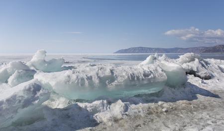 baical: Transparent blue ice hummocks on lake Baikal shore. Siberia winter landscape view. Snow-covered ice of the lake. Big cracks in the ice floe. Stock Photo