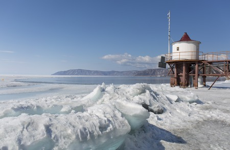 baical: Transparent blue ice hummocks on lake Baikal shore. Siberia winter landscape view with lighthouse. Snow-covered ice of the lake. Big cracks in the ice floe.