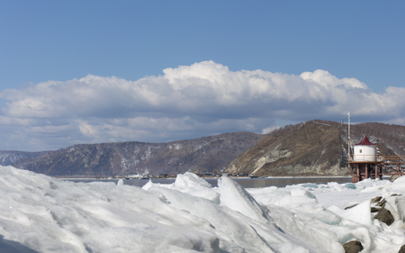 baical: Transparent blue ice hummocks on lake Baikal shore. Siberia winter landscape view with lighthouse. Snow-covered ice of the lake. Big cracks in the ice floe