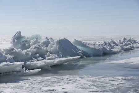 baical: Transparent blue ice hummocks on lake Baikal shore. Siberia winter landscape view. Snow-covered ice of the lake. Big cracks in the ice floe