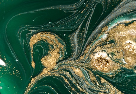 Marbled green abstract background with golden sequins. Liquid marble ink pattern.