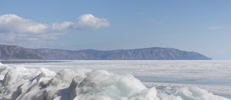 Transparent blue ice hummocks on lake Baikal shore. Siberia winter landscape view. Snow-covered ice of the lake. Big cracks in the ice floe. Soft filter.