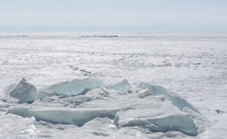 Transparent blue ice hummocks on lake Baikal shore. Siberia winter landscape view. Snow-covered ice of the lake. Big cracks in the ice floe. Standard-Bild