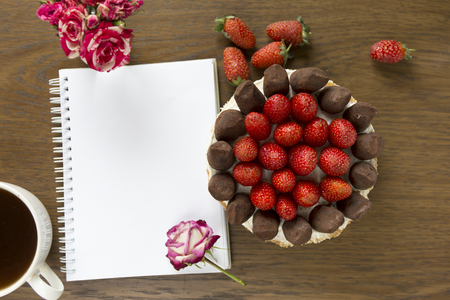 Mockup with blank notepad, cup of coffee and cake. Small rose bouquet. Strawberry and chocolate frash bakery