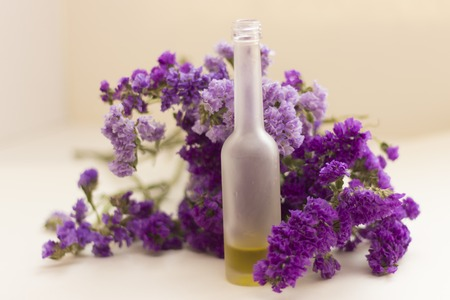 Essential oil in matt bottle on purple flowers blur background.