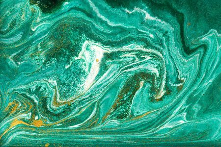 Liquid uneven green marbling pattern with golden glitter and glare of light