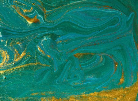 Liquid uneven blue and green marbling pattern with golden glitter and glare of light