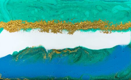 Liquid uneven blue and green marbling pattern with golden glitter and glare of light 스톡 콘텐츠 - 128876929