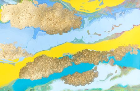Yellow and blue pastel marble pattern with golden glitter. Abstract liquid background. 写真素材