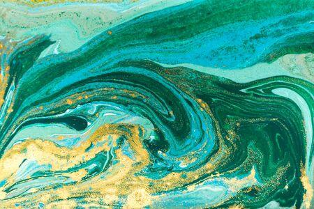 Blue, green and gold glitter pattern. Golden powder liquid texture. 版權商用圖片