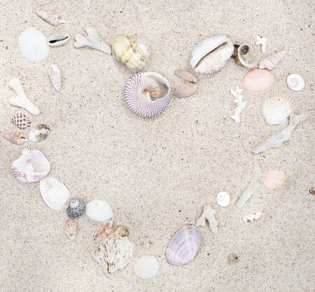 Seashells and corals heart frame on sand background Stock fotó